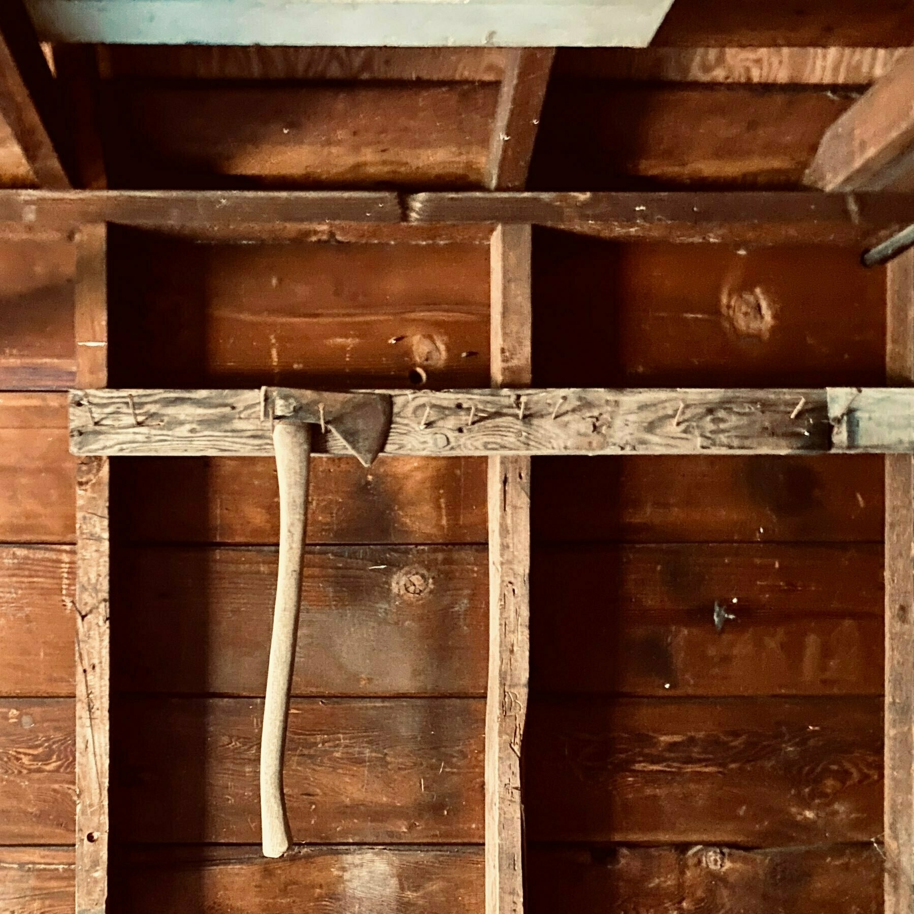 interior of old garage with a grid of wooden planks and an old axe