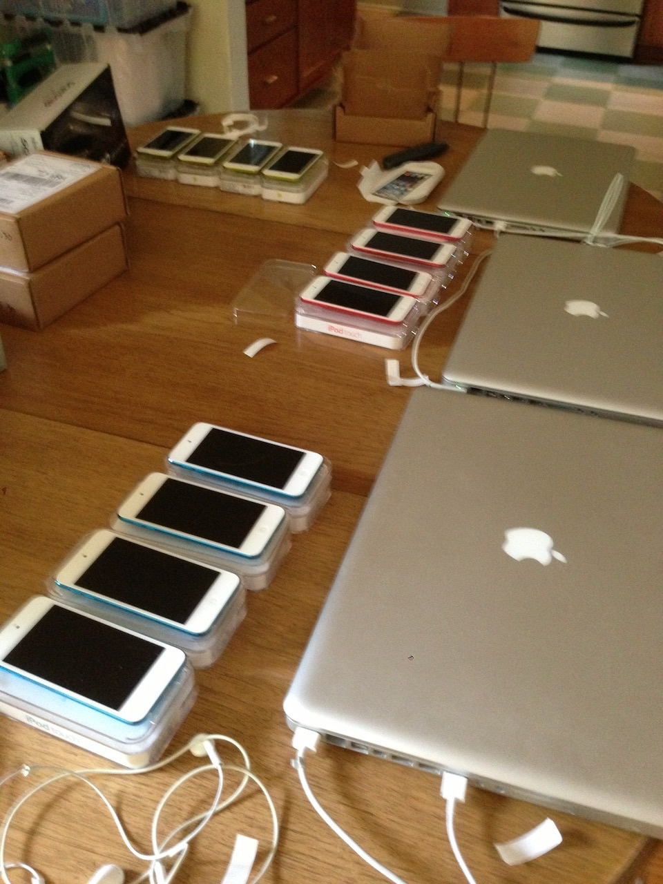 12 iPod touches being provisioned on my dining room table.