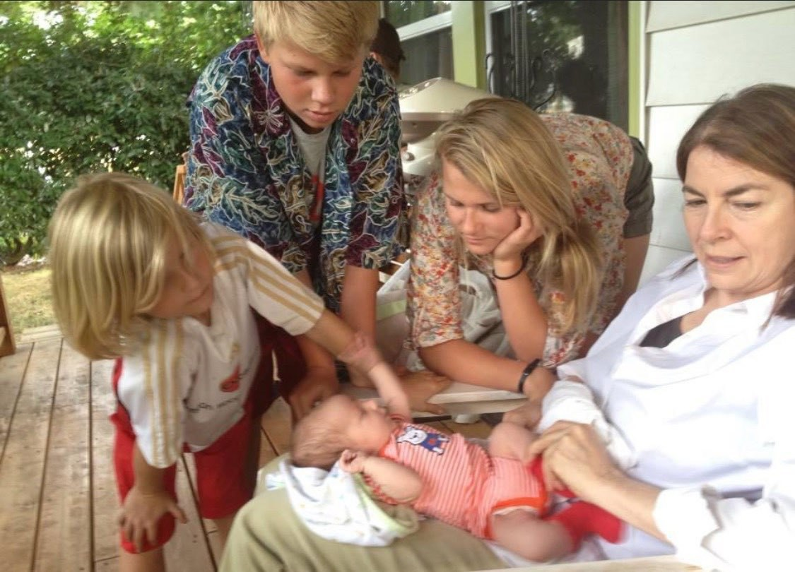 Niece, nephews admire new baby cousin in aunt Jean's lap