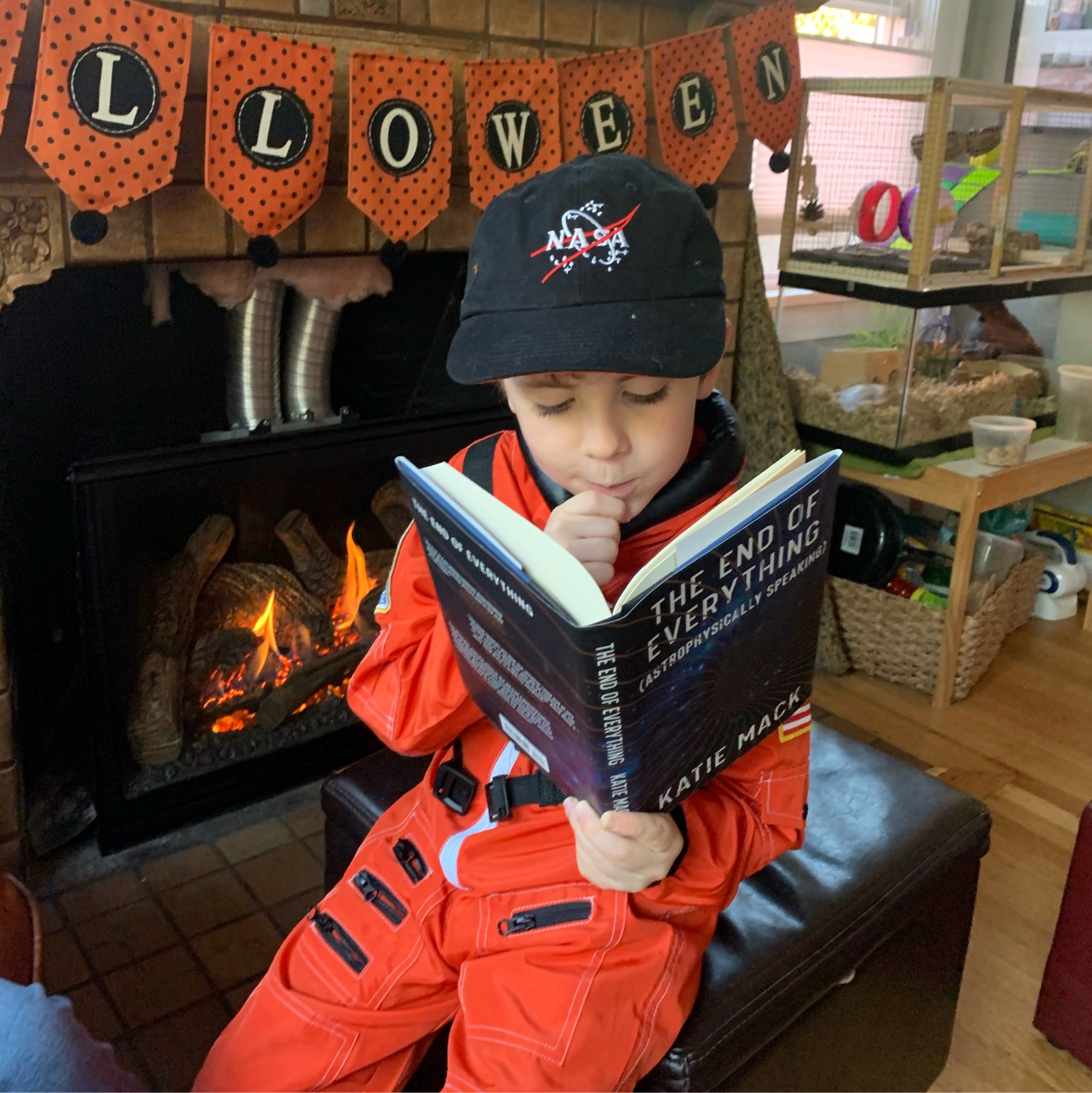 7-year-old in a NASA costume reading astrophysicist Katie Mack's book.