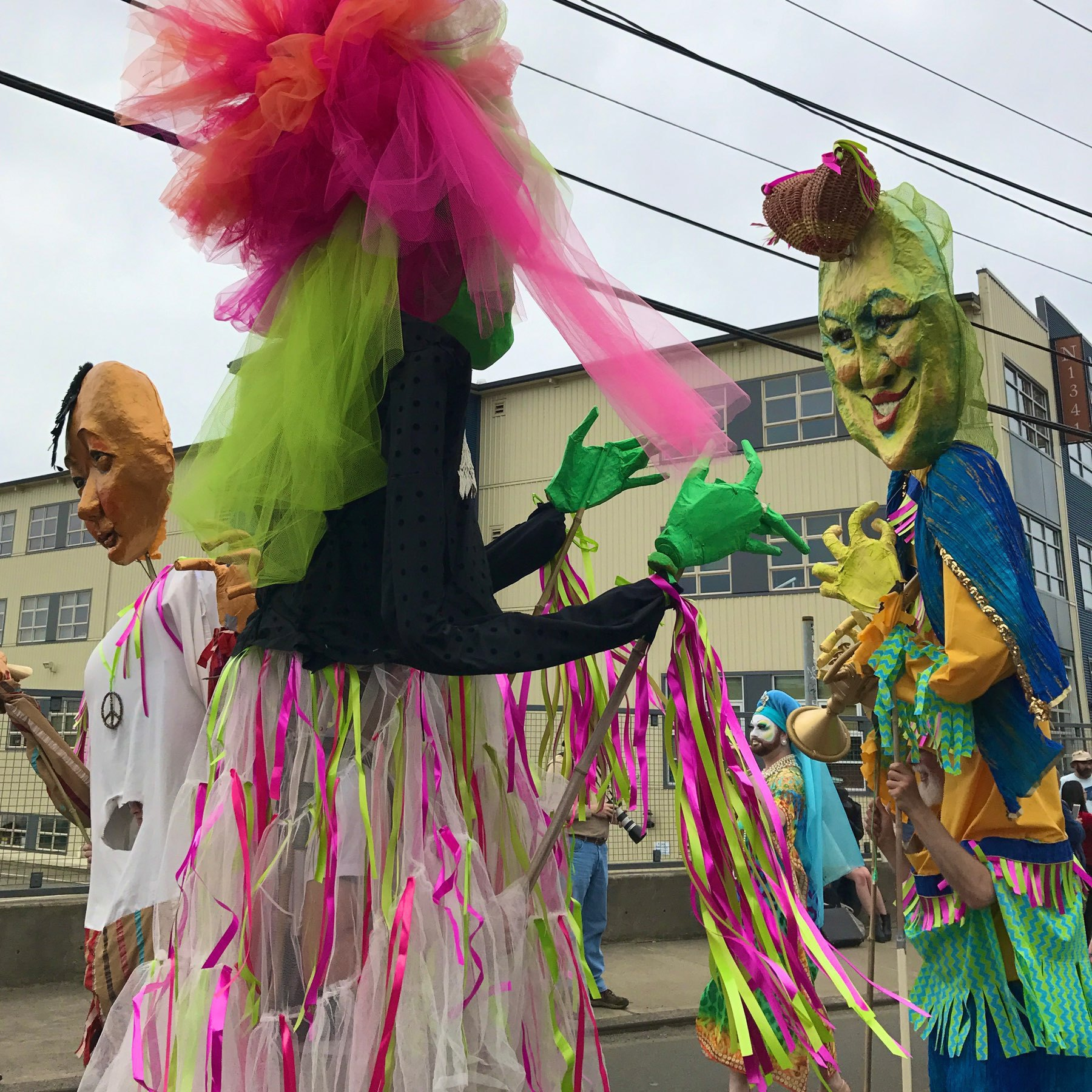 parade marchers in costume wearing large masks and festooned with ribbons