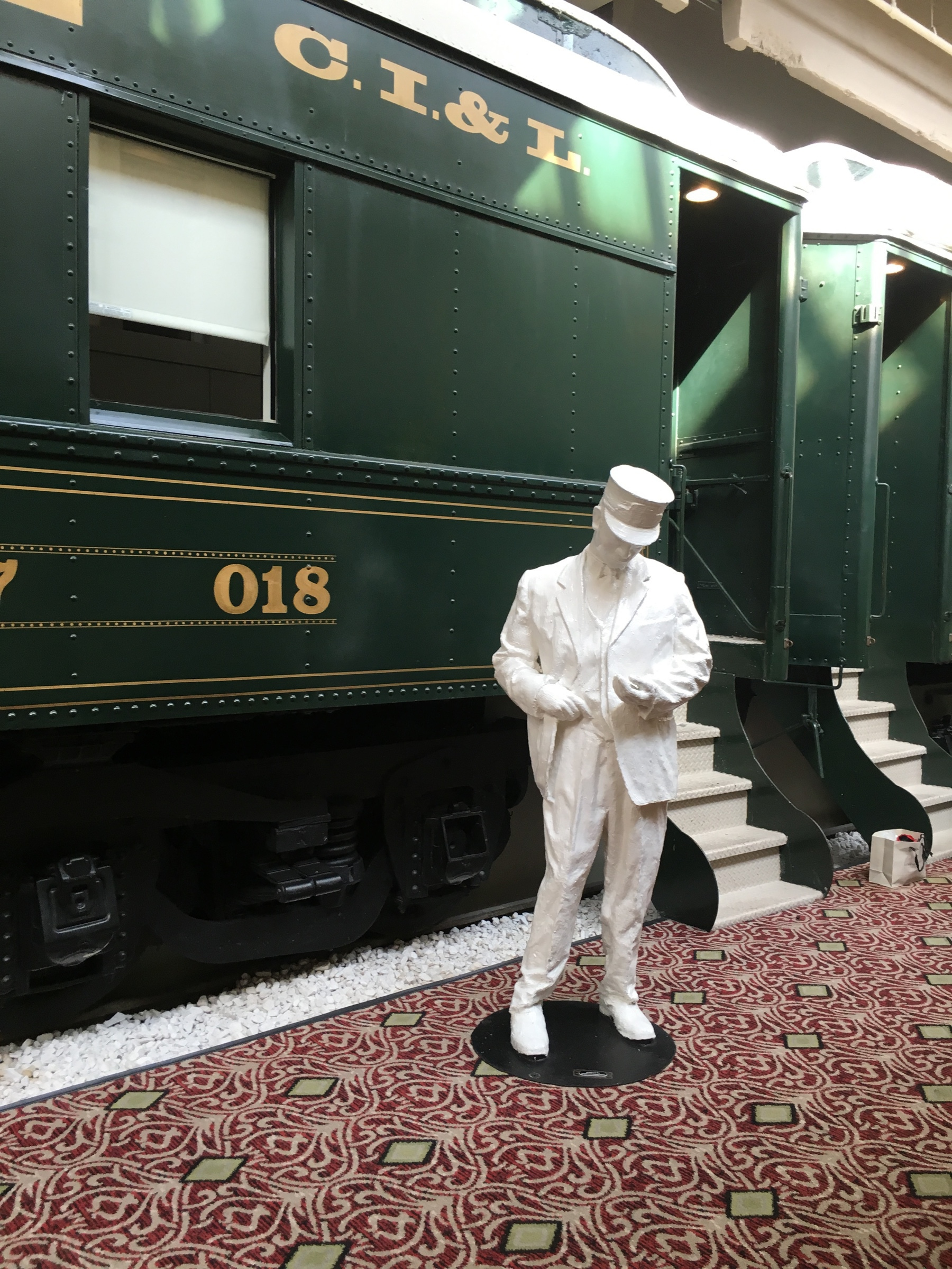 train car hotel room exterior with statue of a conductor