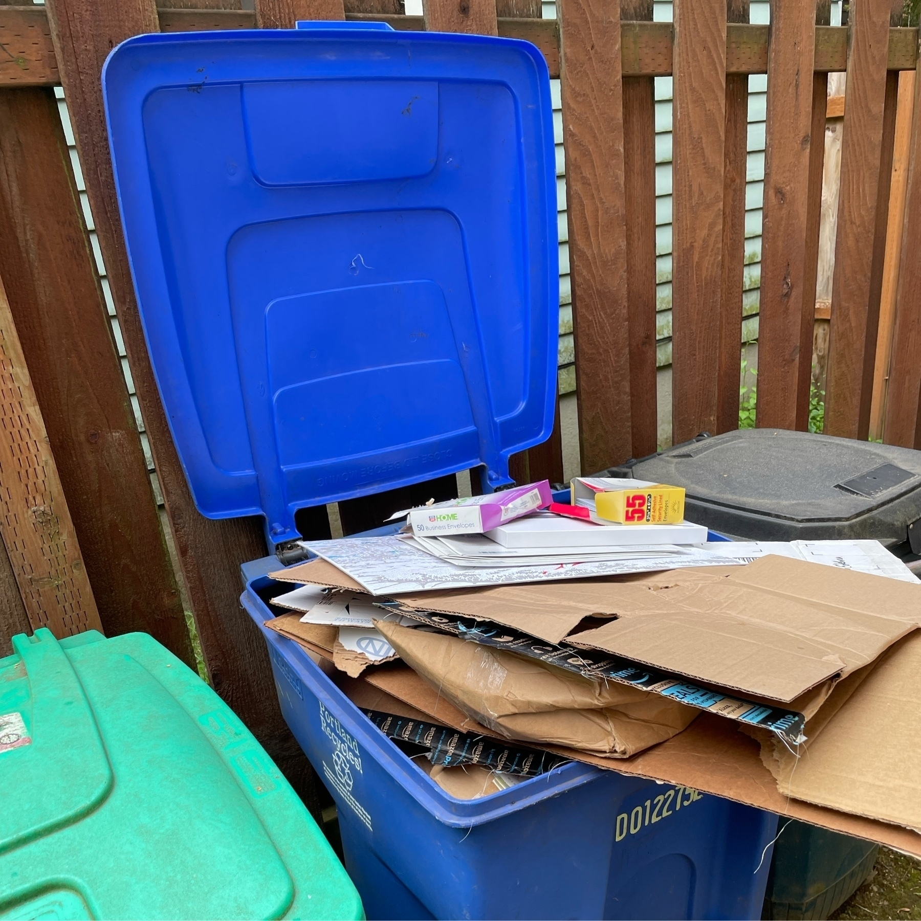 Blue recycling bin filled with paper and cardboard.