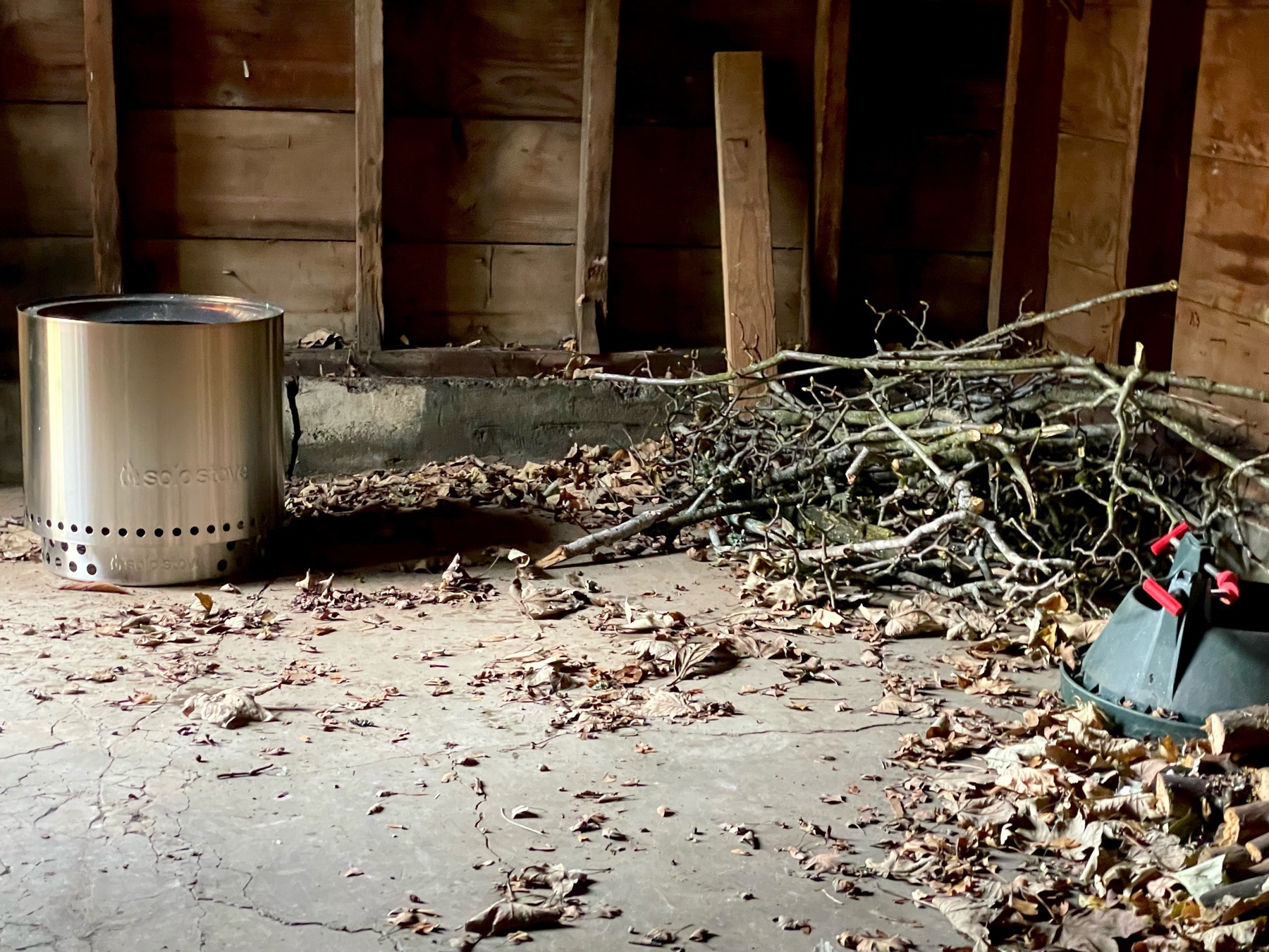 Steel fire pit and pile of branches in wooden garage.