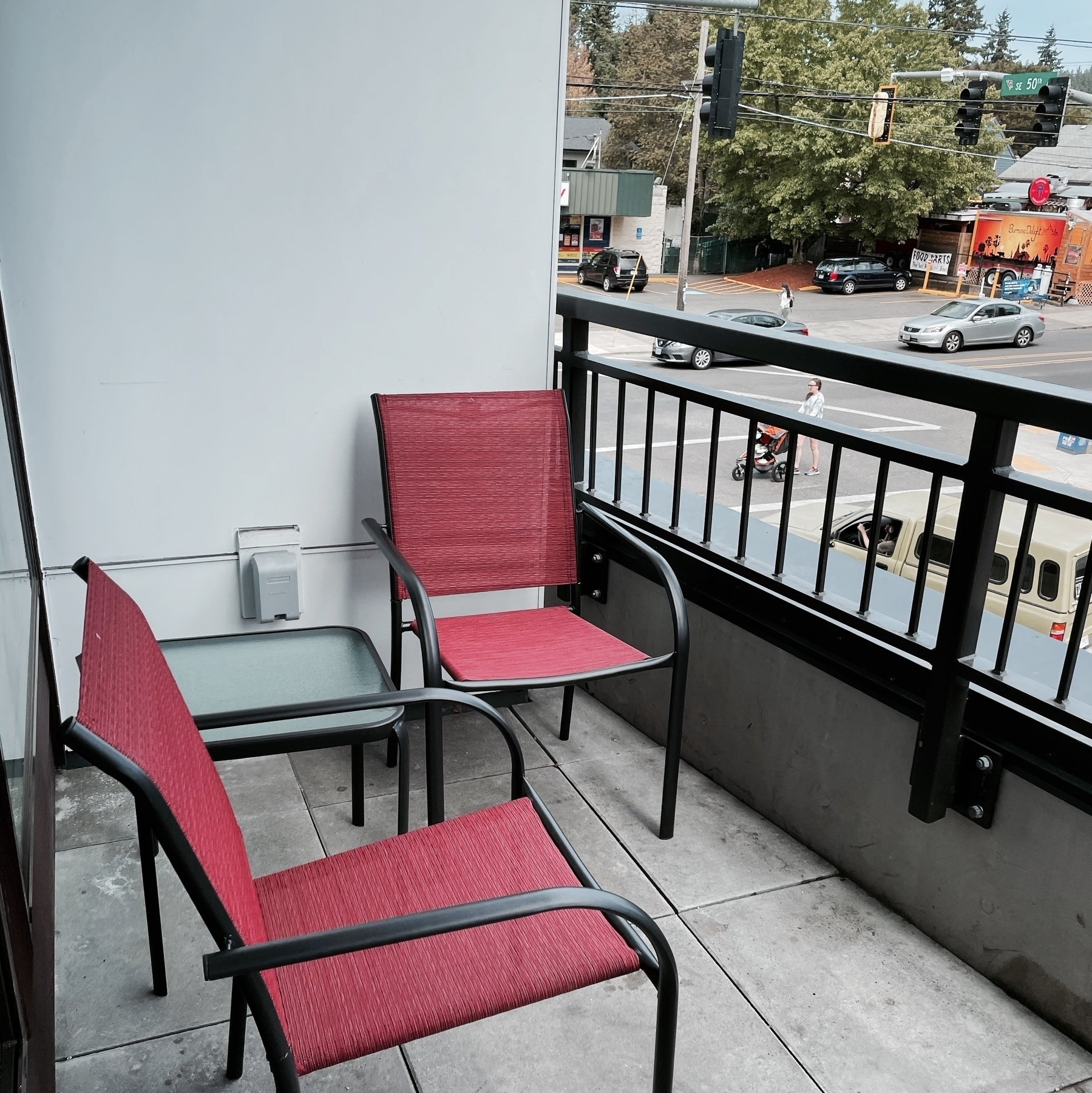 Two red patio chairs, glass-topped end table.